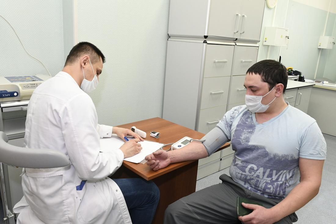 Врач терапевт-кардиолог проводит осмотр перед вакцинацией